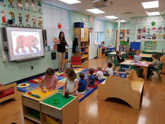 Preschool Teacher, Ms. Cassie, leading a sign language