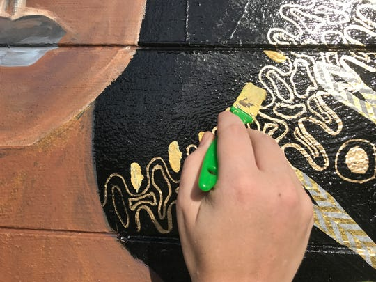 Tallahassee artist Danielle Henn adds a touch of gold to her unity goddess painting on the side of the Salty Fox as part of the Anti-Gravity Project in the Eau Gallie Arts District.