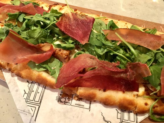 The gorgonzola and pear flatbread ($14) comes topped with gorgonzola cheese, chunks of pear, arugula and speck.