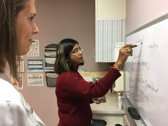 Dr. Kanika Shanker, Summit Health pediatric endocrinologist, reviews the parts of the body that secrete hormones with medical student Hannah Young of McConnellsburg.
