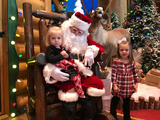Ashlee Hardy sits on Santa's lap while big sister Kaylee Hardy looks on. The two communicated with Santa using sign language Friday at Bass Pro Shops.