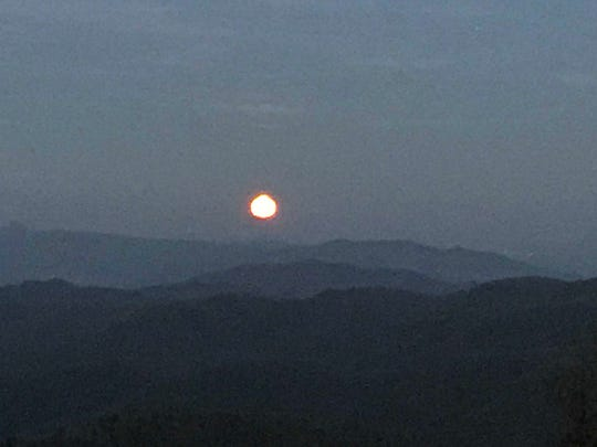 "Sunday night's ""Super Moon"" rises over the mountains, as seen from the Blue Ridge Parkway near Mt. Mitchell. Atmospheric conditions and light refraction gave it an orange color and slightly lumpy shape."