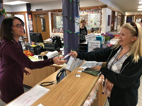 Shasta High School office assistant Laura Dewey, left, takes a check for two tickets to Saturday's NorCal bowl game from Palo Cedro resident Evelyn Millner. Millner's family knows one of the Shasta football players, Troy Lyons, and wants to root him on.