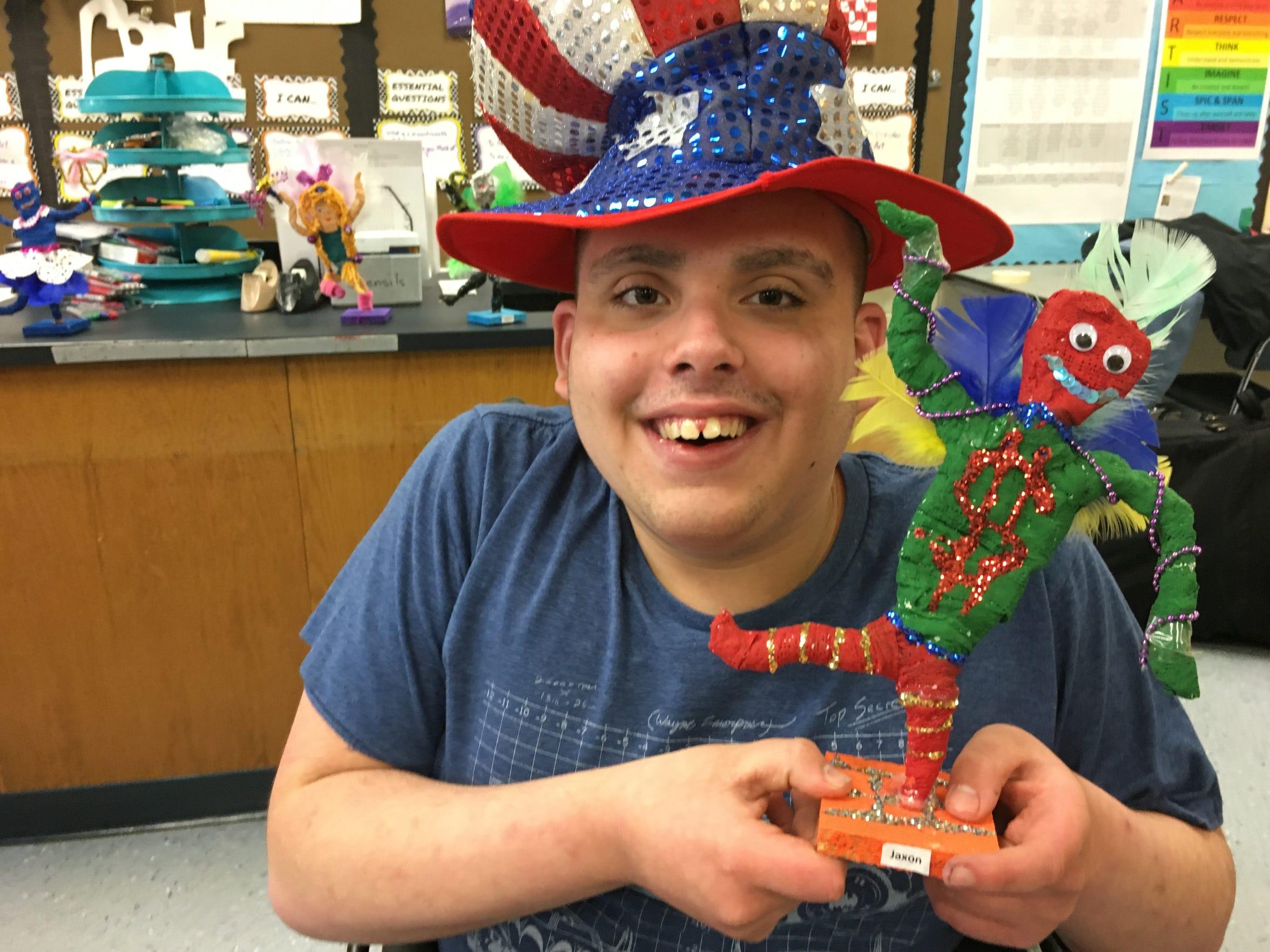 Burlington County Special Services School sophomore Jaxon Keefer, 15 - the student council president - wears a Philadelphia Mummer's costume hat while showing the Mummers-inspired figure he created in art class.