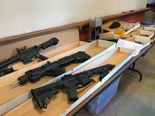 These guns, as well as the kilogram press (center of table), were seized Wednesday during a federal, state and local investigation into a drug-trafficking ring based in Milwaukee.