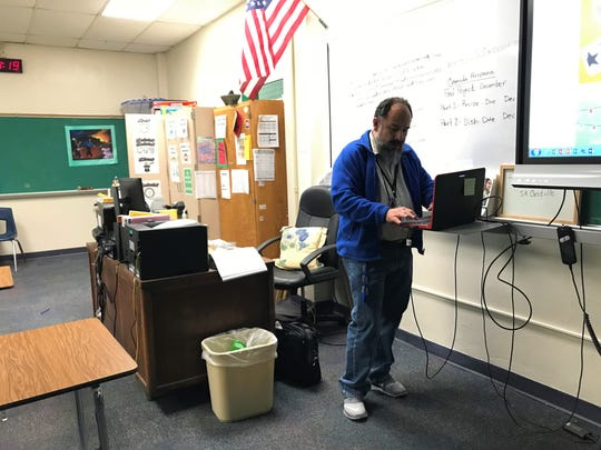 Manuel Castillo, a Spanish teacher at Miller High School, accesses a textbook online and projects it to a screen in the front of the classroom before his class. About half of Castillo's classes, which consist of about 30 students, don't have access to internet or online textbook.
