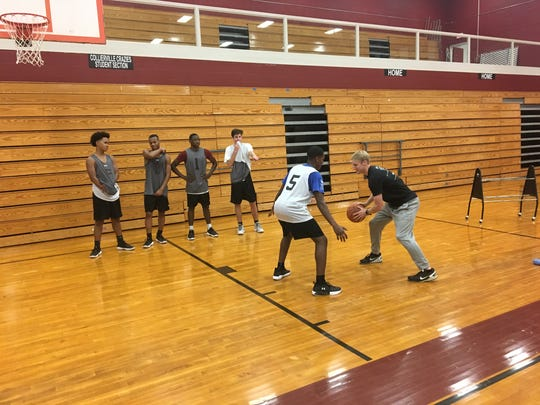Ty Greene showing players a drill at Collierville High School on Thursday, Dec. 7, 2017.
