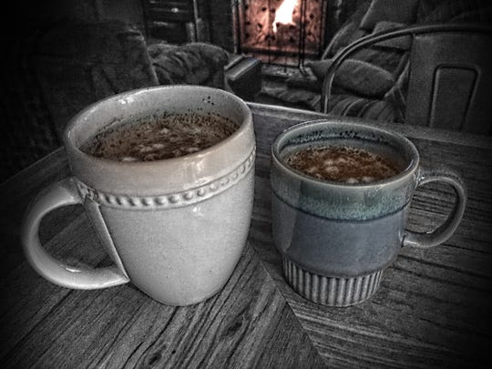 Two cups of hot chocolate with a fireplace in the background.