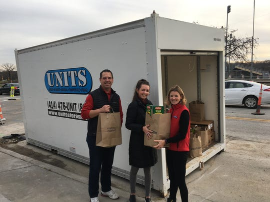 Brian Besler, Lauren Bessler and Janelle Larson put donations in the storage unit. Jim and Janelle Larson own the local UNITS Moving and Portable Storage. They donated a big steel storage container to house all the food our community donates.