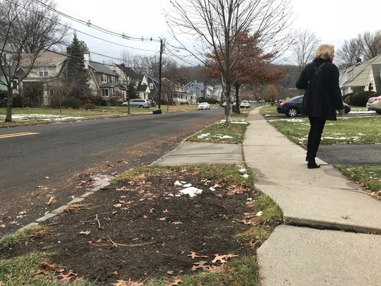 A woman walks past the spot of what was one of 11 trees removed from Undercliff Road in Millburn on Tuesday, Dec. 12, 2017.
