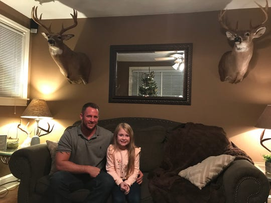 Chloe Phillips, 6, sits with her dad, Zach, in the