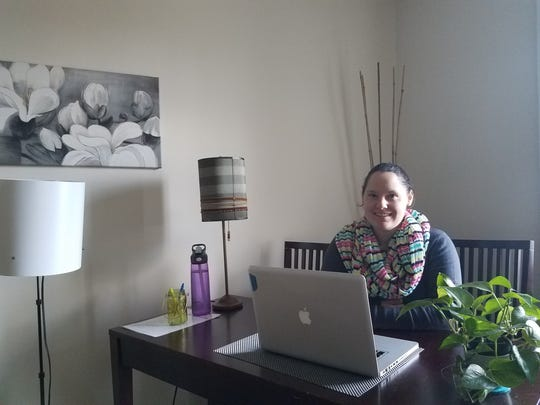 Caylena Cahill sitting at a desk in One Epic Place, a co-working space in New Paltz where she sometimes works.