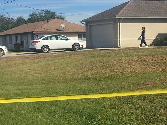 A crime scene investigator works a double homicide in Lehigh Acres on Saturday, Dec. 16, 2017.