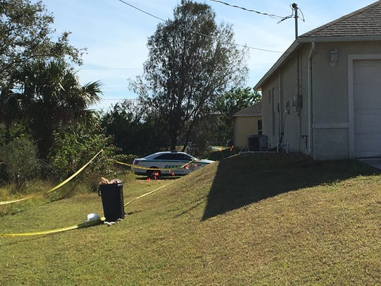 Numerous evidence markers can be seen at the a home in Lehigh Acres where a double homicide occurred.