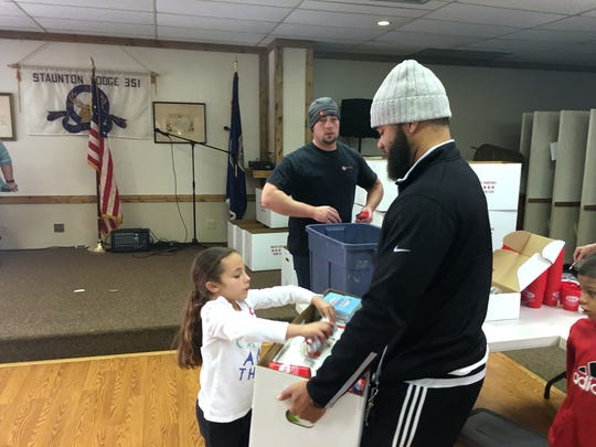 Alayna Fauver adds items to a box carried by Lee High assistant basketball coach Terrell Mickens. The boxes were distributed Saturday afternoon to area families in need.