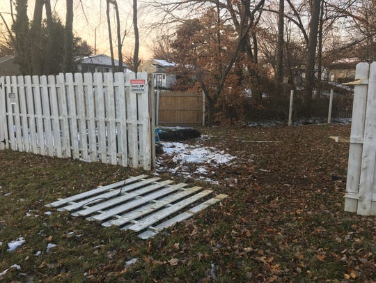 The driver hit the fence and went nose first into the creek, a neighbor said.