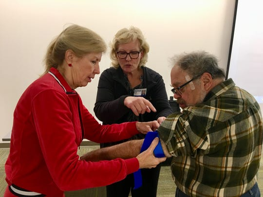 Joy DeFranco of Farmington Hills applies a tourniquet to the arm of Laurence Imerman of Bloomfield Hills as registered nurse Barb Smith offers instruction.