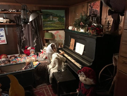 A doll at an antique piano in Tiny Town.