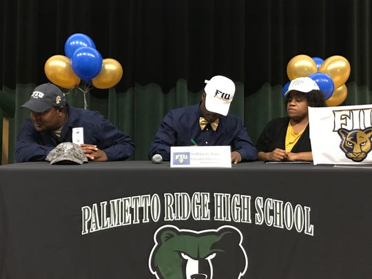 Palmetto Ridge's Demarcus Townsend (center) signed a National Letter of Intent to play football at Florida International on Dec. 20, 2017.