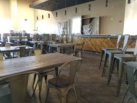 Chairs and tables sit inside the Basin Pub and Grill,