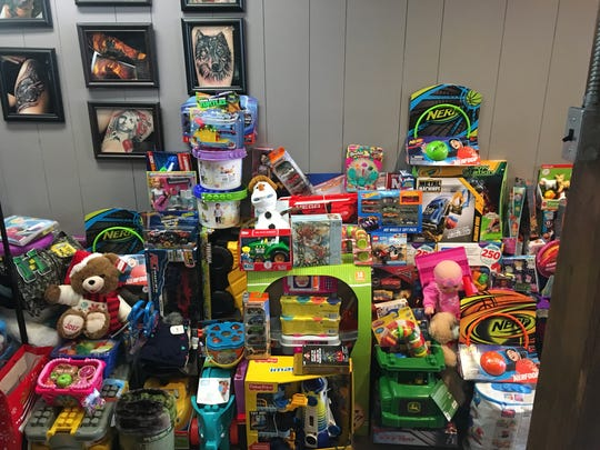Toys lined up on the north wall of MidWest Tattooers in downtown Marshfield. The toys were donated by Marshfield community members and will go to families in the Marshfield area who can't afford gifts for their children.