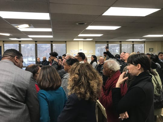 Family and friends scramble for photos as during a swearing-in for five new Montclair police officers at the Municipal Building on Friday, Dec. 22, 2017.