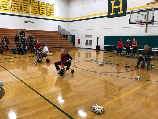 Teachers race across the gym floor in a tricycle race. Liz Miller won in a rout, with Steve Dail a distant second.