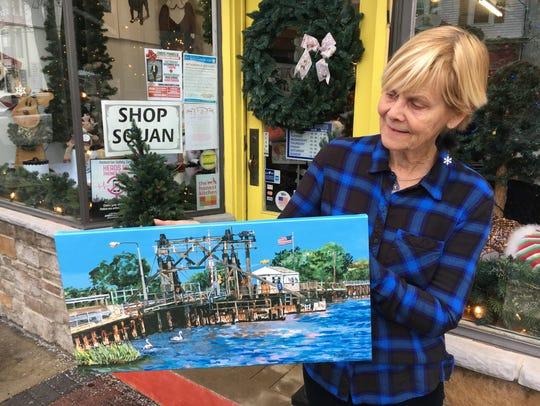 Artist Deborah Meyer, Brick, holds a print of her painting