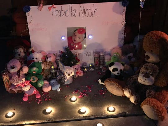 Neighbors gathered in front of this poster with candles in hand to remember 18-month-old Arabella Sanchez.