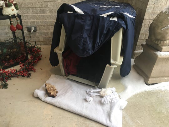A dog crate filled with blankets and toys sits outside