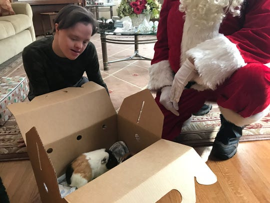 A volunteer from St. Hubert's dressed as Santa Claus delivers guinea pigs, named Brownie and Peanut, to the Geary family in Hanover on Christmas morning, Dec. 25, 2017.
