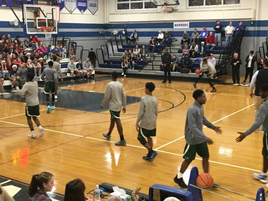 The Long Branch boys basketball team warms up against