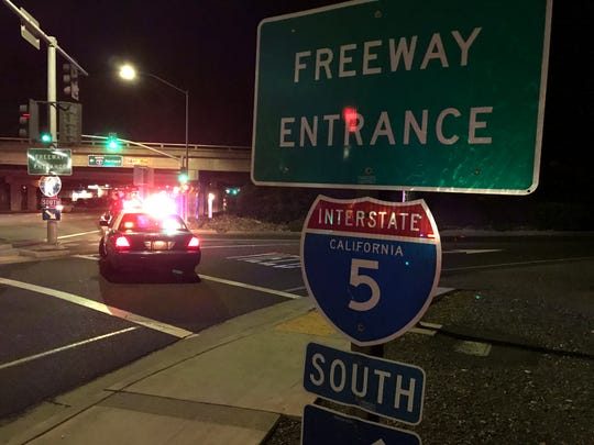Two Redding patrol cars block the southbound on-ramp onto Interstate 5 on Wednesday night due to a pedestrian being struck and killed on the freeway.
