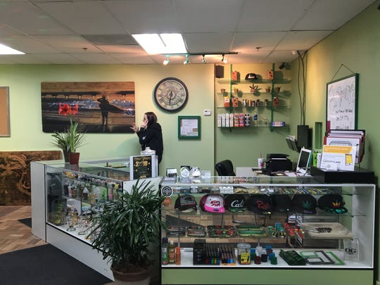 An employee takes a phone call at Cathedral City Care Collective. The marijuana shop opened 12 a.m. Monday, which was the first day marijuana was allowed to be sold in California.