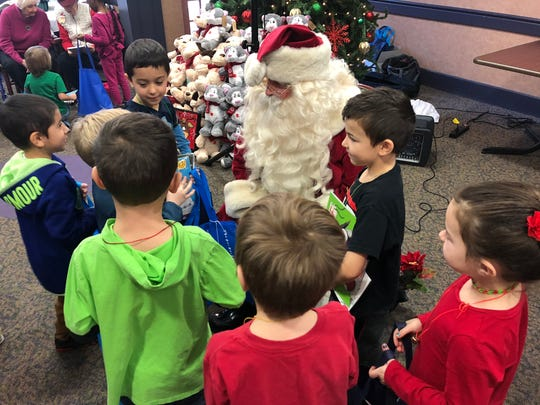 """Santa visits with his student friends, who exchanged many """"thank yous"""" during this photo."""