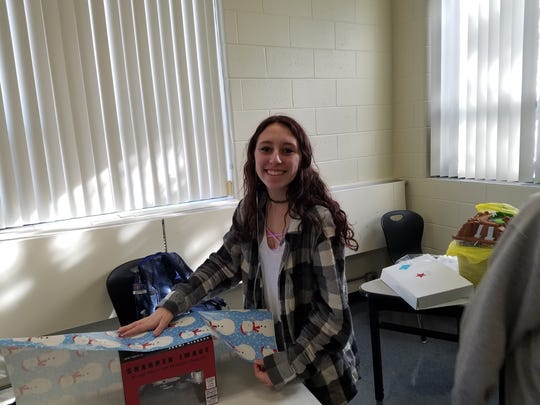 SCVTHS TOPS student Haley LaBracio wraps a present for the Agapé House event.