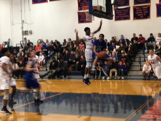Millburn's Bryan Levy (blue) is airborne looking for