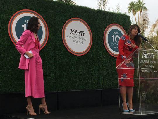 """""""Wonder Woman"""" star Gal Gadot on left presented director Patty Jenkins, at microphone, with the Creative Impact in Directing Award from Variety. (Jan. 3, 2018)"""