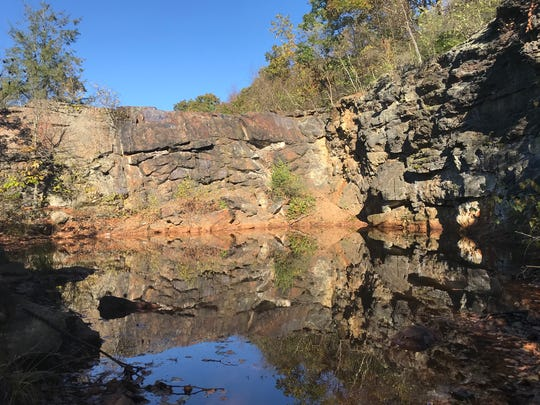 A wall of iron stained rock sits above a shallow pool in the Edison Mine area in Ogdensburg on Oct. 17, 2017.