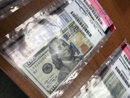 A counterfeit $100 bill inside an evidence bag at the