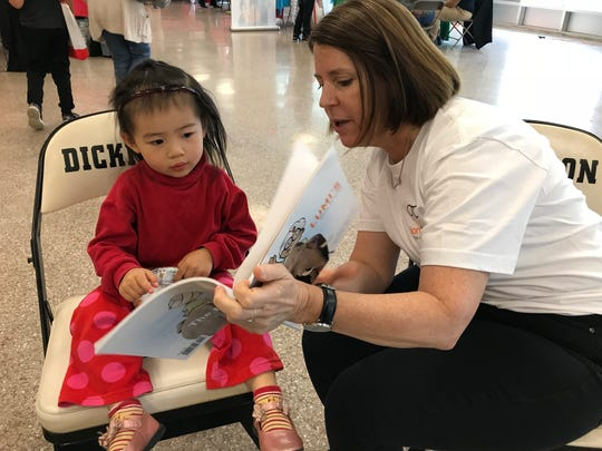 Tara Quinn of Vision to Learn reads to a toddler at the November Literacy Festival that was part of the Red Clay Resource Fair.