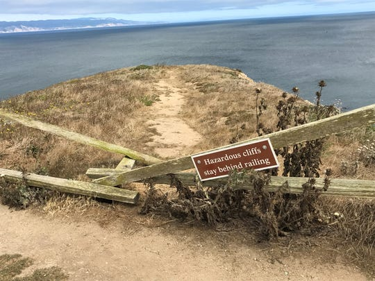 Signs warn visitors about the hazardous cliffs at Chimney
