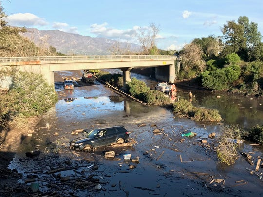 A vehicle sits stranded on flooded Highway 101 in Montecito on Wednesday, the day after dozens of homes were swept away or heavily damaged in debris flows set off by a storm.