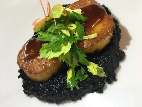 The Fat Snook in Cocoa Beach is known for its inventive takes on seafood like these jumbo scallops served over squid ink polenta.