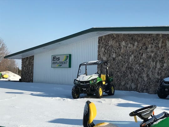 A snow-covered lawnmower sits outside of Eis Implement in Two Rivers Jan. 9, 2018.