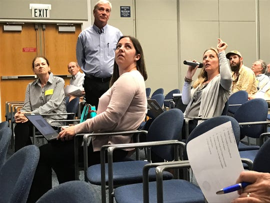 Matt Morrison of the South Florida Water Management District, standing, and participants at a Dec. 5 public meeting, look at reservoir plans on an overhead screen as Dawn Shirreffs of the Everglades Foundation asks a question.