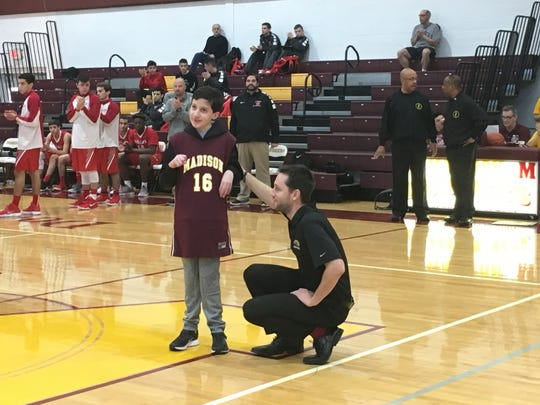 Madison boys basketball coach Joe Reel introduces brain-tumor survivor Spencer Jacovini to the crowd.