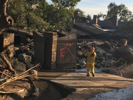 A firefighter walks down to a home inundated with mud