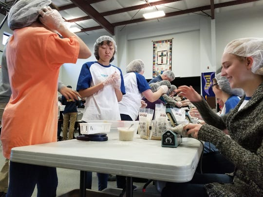 Volunteers help assemble food packages on Saturday, January 13, 2018 at Messiah Lutheran Church in Mauldin.