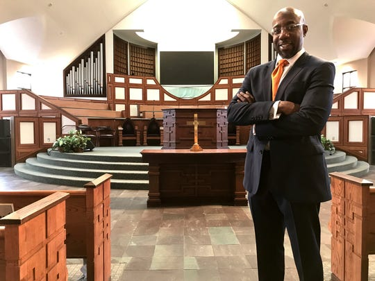In this Thursday, Jan. 11, 2018 photo, the Rev. Raphael Warnock stands in the sanctuary of Ebenezer Baptist Church in Atlanta. Warnock is senior pastor of the congregation once led by the Rev. Martin Luther King Jr. (AP Photo/Jeff Martin)